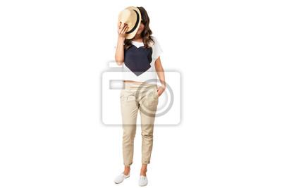 junge modische Brünette versteckt Gesicht mit einem stilvollen Hut