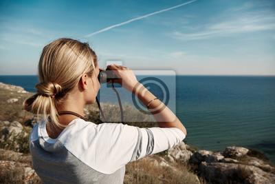 Junge schöne frau wanderer sucht durch fernglas auf dem berg