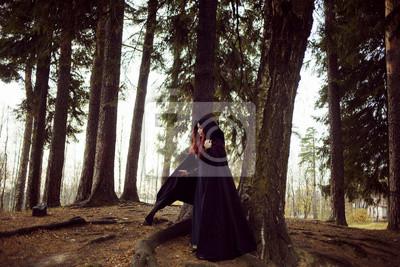 Junge schöne und geheimnisvolle frau im wald, in schwarzem