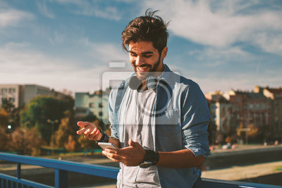 Fototapete Junger glücklicher Mann, der einen Smartphone in der Stadt verwendet