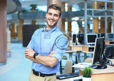 Fototapete Junger Mann, der überzeugt und positiv im Berufsarbeitsplatzbüro mit Raum aufwirft.