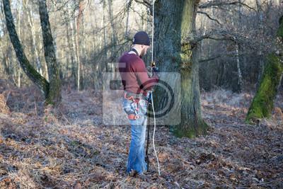 Kletterausrüstung Baum : Junger mann klettertraining im winter aufseilen und abseilen