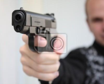 Junger Mann mit dem Ziel mit Pistole in der Hand