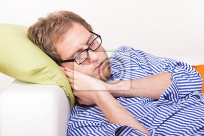 Junger Mann schläft auf der Couch