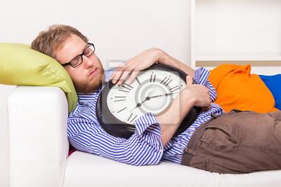 Junger Mann schläft auf der Couch mit großen Uhr