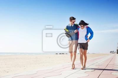 Junges Paar zu Fuß auf einer Promenade am Meer