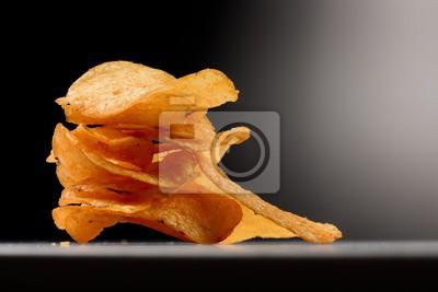 Fototapete Kartoffelchips gestapelt im Spotlight - vor schwarzem Hintergrund