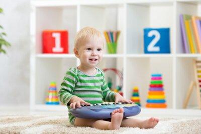 Fototapete Kid boy playing toy piano in nursery