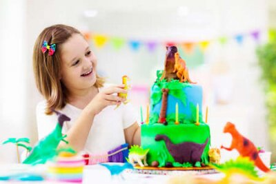 Fototapete Kids birthday party. Dinosaur theme cake. Little girl blowing candles and opening gifts. Children event. Decoration for dinosaurs themed celebration.