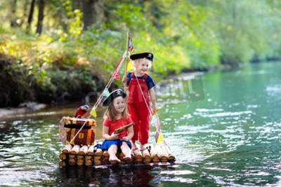 Fototapete Kids dressed in pirate costumes and hats with treasure chest, spyglasses, and swords playing on wooden raft sailing in a river on hot summer day. Pirates role game for children. Water fun for family.
