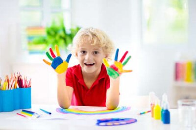 Fototapete Kids paint. Child painting in white sunny study room. Little boy drawing rainbow. School kid doing art homework. Arts and crafts for kids. Paint on children hands. Creative little artist at work.