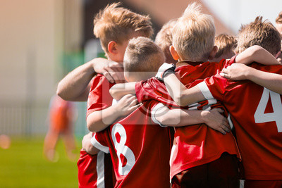 Fototapete Kids Play Sports Game. Children Sporty Team United Ready to Play Game. Children Team Sport. Youth Sports For Children. Boys in Sports Jersey Red Shirts. Young Boys in Soccer Sportswear
