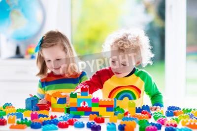 Fototapete Kind spielt mit bunten Spielsachen. Kleines Mädchen und lustig lockiges Baby mit pädagogischen Spielzeug Blöcke. Kinder spielen bei Tagespflege oder Vorschule. Verwirrung im Kinderzimmer. Kleinkinder