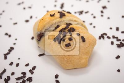 Fototapete kleiner Schokoladen-Croissant mit Schokoladenstreuseln vor weißem Hintergrund