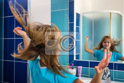Fototapete: Kleines mädchen im badezimmer schaut in den spiegel, während