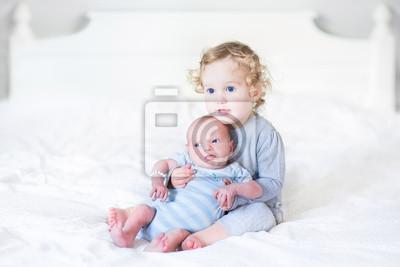 Kleinkind mädchen die ihr neugeborenes baby bruder auf einem