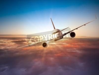 Fototapete Kommerzielle Flugzeug fliegen über Wolken in dramatischen Sonnenuntergang Licht