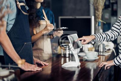 Fototapete Kunden-Selbstbedienungsbestellungsgetränkemenü mit Tablettenschirm an der Cafégegenstange, Verkäufercafé akzeptieren Zahlung durch Mobile Digital-Lebensstilkonzept Blank-Raum für Anzeige des Designs.