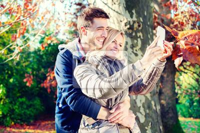 lächelnde Paar unter Selfie im Herbst