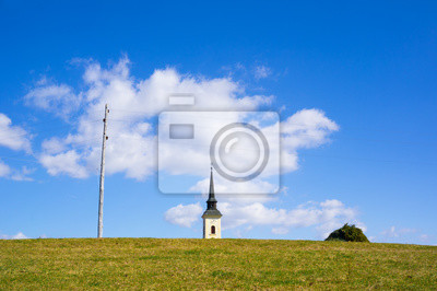 Land in slowenien - wiese mit grünem gras, kirche mit turm und ...