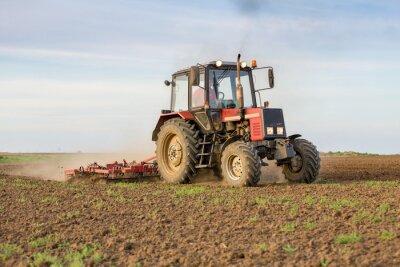 Fototapete Landwirt kultiviert Ackerland vor der Aussaat