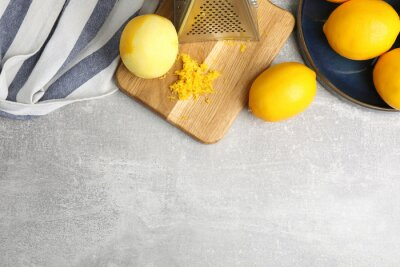 Fototapete Lemon zest and fresh fruits on grey table, flat lay. Space for text