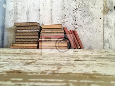 Libri antichi impiliti su tavolo legno und muro grezzo vintage ...