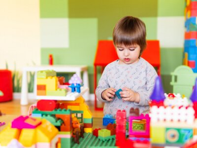 Fototapete Little boy playing in nurseroom with colorful constructor. Educational toy block in toddler hands. Kid is busy with toy bricks.