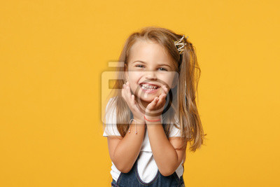 Fototapete Little cute child kid baby girl 4-5 years old wearing light denim clothes isolated on pastel yellow wall background, children studio portrait. Mother's Day, love family, parenthood childhood concept.
