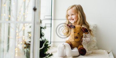 Fototapete little girl with a plush deer sitting on the window. A child looks out the window and is waiting for Christmas, Santa Claus