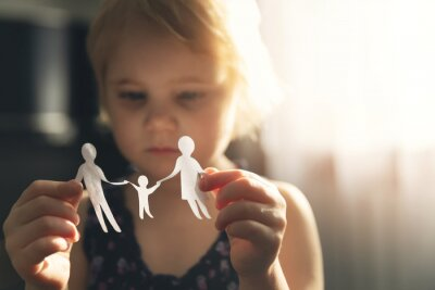 Fototapete little girl with paper family in hands. concept of divorce, custody and child abuse