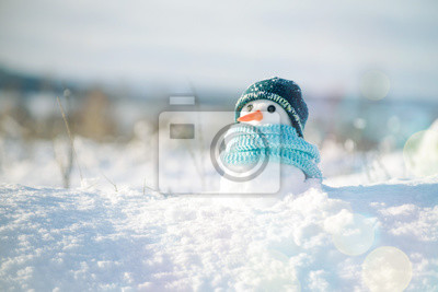 Fototapete Little snowman in a cap and a scarf on snow in the winter. Christmas card with a lovely snowman, copy space