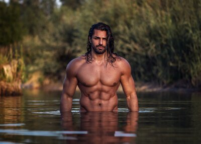 Fototapete Long haired bearded muscular man shirtless stands waist deep in the water. Aquaman in the water. Tanned attractive guy with long dark wet hair