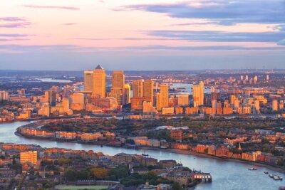 Fototapete Luftaufnahme des östlichen Londoner Finanzbezirks der Canary Wharf Docklands, die durch Themse-Fluss umkreist werden, mit Gebäuden, die durch bunten Sonnenuntergang beleuchtet werden