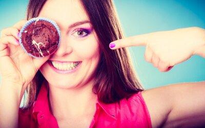 Fototapete Lustige Frau hält Kuchen in der Hand, die ihr Auge