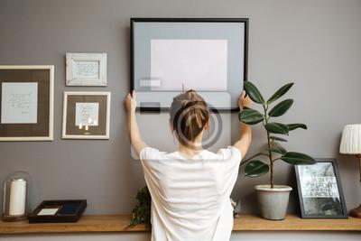 Fototapete Mädchen, das einen Rahmen an einer grauen Wand hängt