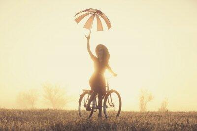 Fototapete Mädchen mit Regenschirm auf dem Fahrrad in der Natur in Sonnenaufgang Zeit