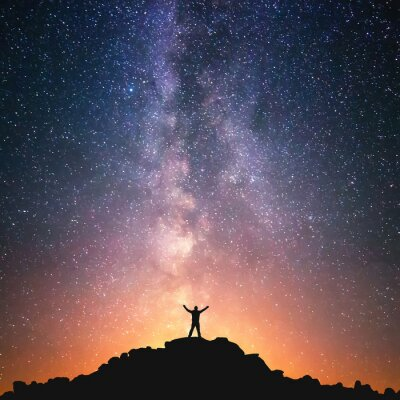 Fototapete Man and the Universe. A person is standing on the top of the hill next to the Milky Way galaxy with his hands raised to the air.