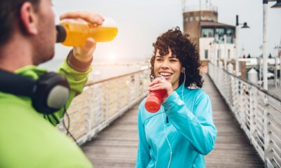 Fototapete Man and woman drinking energy drink from bottle after fitness sport exercise