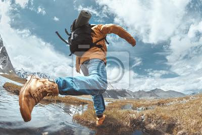 Fototapete Man hiker jumps across water in mountain area