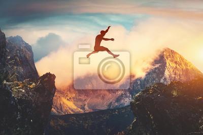 Fototapete Man jumping between mountains at sunset.