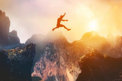 Fototapete Man jumping between rocks. Overcome a problem for a better future