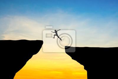 Fototapete Man springen durch die Lücke zwischen hill.man springen über Cliff auf Sonnenuntergang Hintergrund, Business-Konzept-Idee