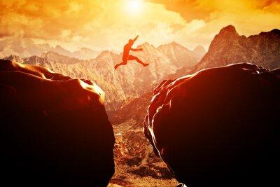 Fototapete Man springt über Abgrund zwischen zwei Bergen bei Sonnenuntergang