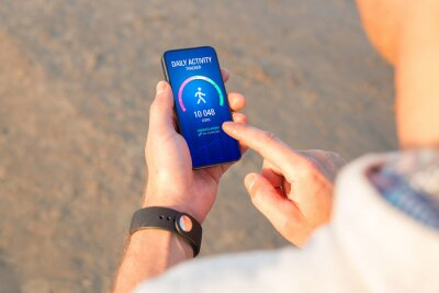 Fototapete Man using daily activity tracking app on mobile phone showing 10 000 steps daily goal achievement