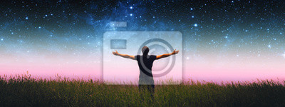 Fototapete Man with arms wide open standing on the grass field against the night starry sky. Elements of this image furnished by NASA.