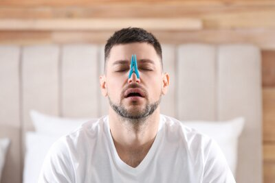 Fototapete Man with clothespin suffering from runny nose in bedroom