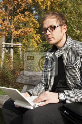 Mann in den Gläsern auf Laptop