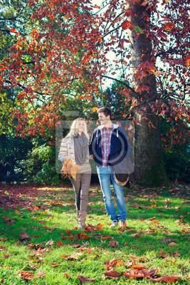 Mann und Frau gehen Hand in Hand im Herbst Park