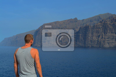 Mann von hinten stehend am Meer mit Blick auf Küste Klippen und Wasser, Teneriffa, Spanien.